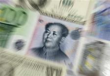 Различные валюты мира, включая юань, доллар и евро, 9 февраля 2011 г. Управляющие европейских хедж-фондов делают ставку на резкое замедление экономического роста Китая в 2012 году, которое скажется на доходах компаний и ценах на сырье, подогреваемых в последние годы второй экономикой мира. REUTERS/Kacper Pempel