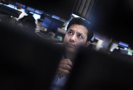 A trader watches screens at his desk at the Frankfurt stock exchange January 16, 2012. REUTERS/Alex Domanski