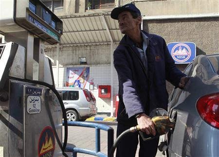 A worker pumps fuel at a petrol station in Cairo January 16, 2011. REUTERS/Asmaa Waguih