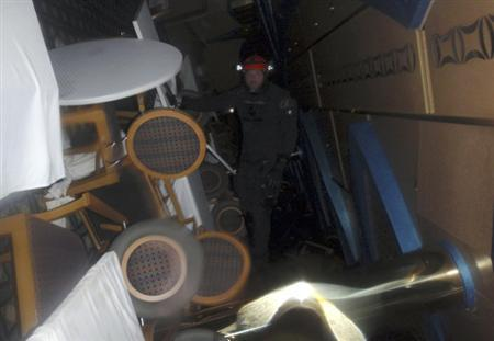 An Italian Coast guard diver inspects inside the Costa Concordia cruise ship that ran aground off the west coast of Italy, at Giglio island January 16, 2012. REUTERS/Guardia Costiera/Handout