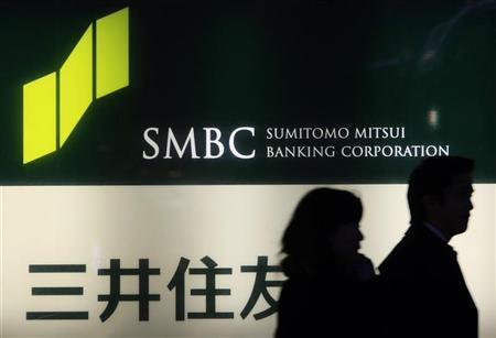 People walk past a signboard of Sumitomo Mitsui Banking Corporation in Tokyo February 8, 2010. REUTERS/Kim Kyung-Hoon