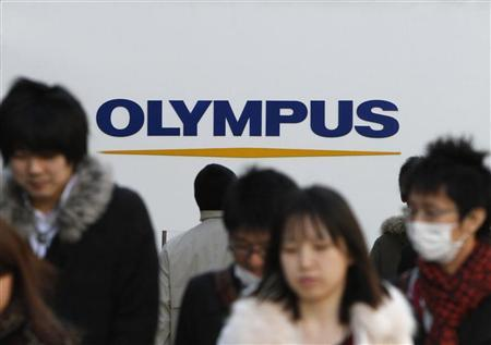 People walk past a signboard of Olympus Corp outside its showroom in Tokyo January 12, 2012.  REUTERS/Toru Hanai