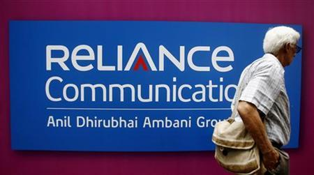 A man walks past a logo of Reliance Communication before the Annual General Meeting in Mumbai September 22, 2009. REUTERS/Arko Datta/Files