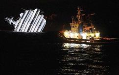 Судно, специализирующееся на сборе нефти, не фоне затонувшего лайнера Costa Concordia у берегов Италии 16 января 2012 года. Спасатели произвели во вторник три контролируемых взрыва, чтобы попасть в до этого не доступные части потерпевшего крушение итальянского круизного лайнера в надежде найти выживших. REUTERS/ Max Rossi