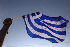 Демонстрант держит греческий флаг около здания парламента в Афинах 5 июня 2011 года. Грецию ждет дефолт, но скорее всего, он будет контролируемым, сообщило во вторник рейтинговое агентство Fitch. REUTERS/Pascal Rossignol