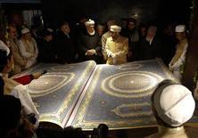 Каллиграф Мухаммед Сабир Хедри (в центре справа) стоит рядом с крупнейшим в мире Кораном во время церемонии представления книги публике в библиотеке Hakim Nasir Khosrow Balkhi в Кабуле 12 января 2012 года. Каллиграф из Афганистана создал самый большой Коран в мире, потратив на это пять лет кропотливой работы, передает Кабульский культурный центр со ссылкой на министерство хаджа и религиозных отношений Афганистана. REUTERS/Mohammad Ismail
