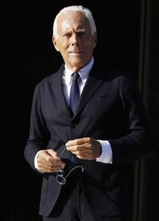 Italian designer Giorgio Armani poses for photographers as he leaves the opening ceremony of the Armani Hotel Milano in Milan November 10, 2011. REUTERS/Alessandro Garofalo