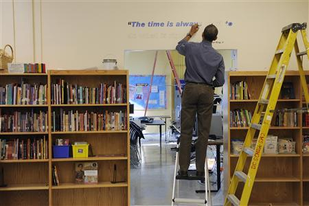 President Obama paints a quotation attributed to slain civil rights leader Martin Luther King Jr during a day of service in King's honor at the Browne Education Campus school in Washington, January 16, 2012.  REUTERS/Jonathan Ernst