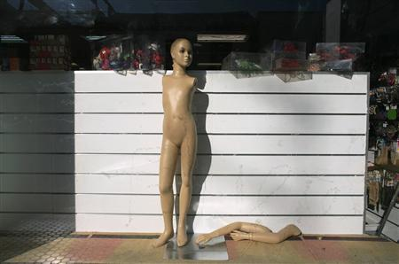 A dummy is seen in a shop that is closing down in the Andalusian capital of Seville January 17, 2012.  REUTERS/Marcelo del Pozo