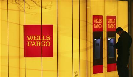 A man uses an automated teller machine (ATM) at a Wells Fargo Bank branch on a rainy morning in Washington January 17, 2012. REUTERS/Gary Cameron