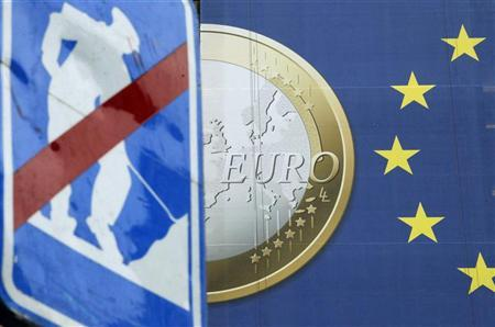 A road sign is seen near a banner of a euro coin on the facade of the European Commission headquarters before an European Union summit in Brussels December 8, 2011.  REUTERS/Francois Lenoir