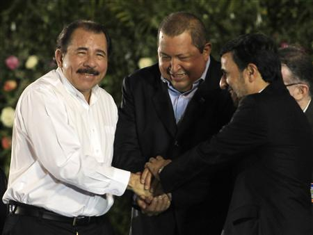 Nicaragua's President Daniel Ortega shakes hands with Venezuela's President Hugo Chavez (C) and Iran's President Mahmoud Ahmadinejad (R) before swearing-in for his second term as president at the Revolution Square in Managua January 10, 2012. REUTERS/Oswaldo Rivas