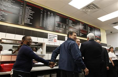 Republican presidential candidate and Texas Governor Rick Perry (2nd L) greets the staff at the The Drive-In Restaurant in Florence, South Carolina, January 17, 2012. REUTERS/Jim Young