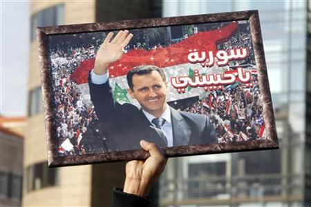 A protester holds up a picture of Syria's President Bashar al-Assad during a protest in front of the the U.N. headquarters in Beirut, January 13, 2012, against U.N. Secretary-General Ban Ki-moon's visit to Lebanon. REUTERS/ Sharif Karim