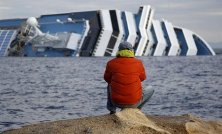 The Costa Concordia cruise ship (rear) that ran aground off the west coast of Italy is seen at Giglio island January 18, 2012. REUTERS/ Max Rossi