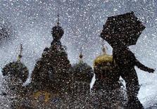 Отражение в луже Храма Спаса на Крови в Санкт-Петербурге 16 июля 2004 года. Всемирный банк в среду понизил прогноз роста ВВП России в 2012 году до 3,5 процента с 3,8 процента наравне с негативной переоценкой развития мировой экономики. REUTERS/Alexander Demianchuk