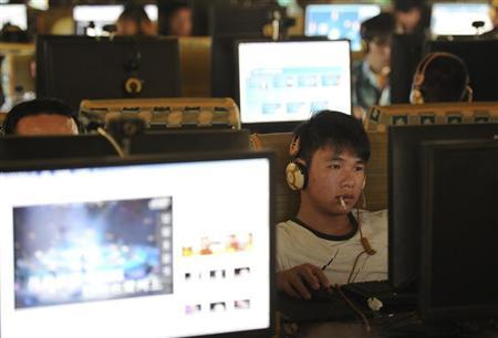 A man smokes as he uses a computer at an internet cafe in Hefei, Anhui province, September 15, 2011.      REUTERS/Stringer  CHINA OUT. NO COMMERCIAL OR EDITORIAL SALES IN CHINA