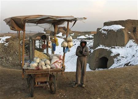 An Afghan boy stands next to his popcorn stall as he waits for customers on a road in Kabul January 8, 2012. REUTERS/Mohammad Ismail