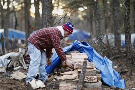 Steve ''Pockets'' gathers firewood to heat the inside of his tent, that is part of a homeless community near Lakewood, New Jersey January 9, 2012.  REUTERS/Lucas Jackson