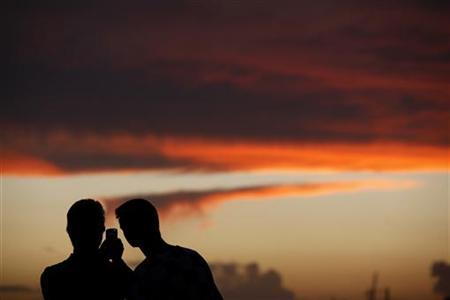 Tourists use a mobile phone to take a photo of the sunset in the town of Sliema in Valletta's Marsamxett Harbour October 26, 2011.  REUTERS/Darrin Zammit Lupi