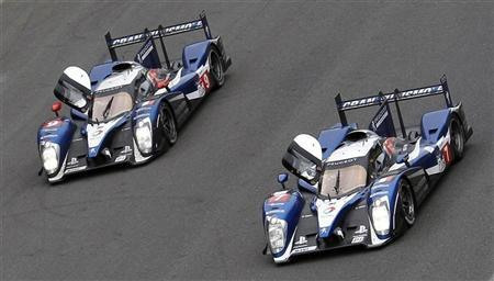 Peugeot 908 number 7 and 9 (L) cross the finish line at the Le Mans 24-hour sportscar race in Le Mans, central France June 12, 2011. REUTERS/Regis Duvignau