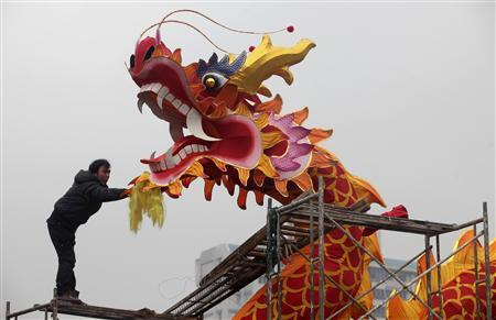 A worker installs a dragon decoration for the upcoming Chinese Lunar New Year in Wuhan, Hubei province, January 18, 2012.  REUTERS/Stringer