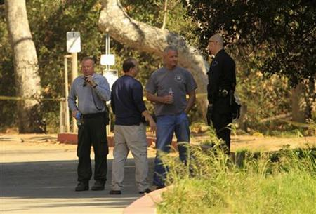 Los Angeles County coroners and Los Angeles police officers are seen in Bronson Canyon, where dog walkers discovered an unidentified man's head yesterday in Los Angeles, California, January 18, 2012. REUTERS/Al Seib/Pool
