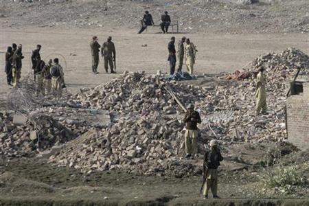 Police and military officials stand near the rubble of a paramilitary building levelled by a suicide bomb attack in Bannu, northwest Pakistan December 24, 2011. REUTERS/Zahid Mahmmad