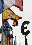 Национальные флаги и символ евро возле здания Европарламента в Брюсселе 30 августа 2011 года. Fitch может понизить рейтинги шести стран еврозоны, поставленных на пересмотр в конце прошлого года, на одну или две ступени, сообщил директор группы суверенных рейтингов Европы Эд Паркер. REUTERS/Francois Lenoir