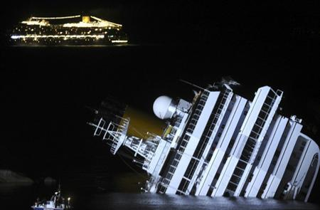 The cruise ship Costa Serena sails as its sister ship Costa Concordia cruise ship lays on its side after it ran aground off the west coast of Italy at Giglio island January 18, 2012. REUTERS/Stringer