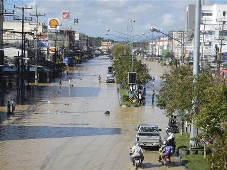 Residents wade through a flooded road in Had Yai district of Songkhla province, southern Thailand, January 2, 2012. REUTERS/Stringer