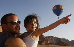 """Девочка показывает пальцем на воздушный шар в израильском парке Тимна 16 октября 2008 года. Они могут быть легкими, например: """"Укусила бы акула динозавра во время драки?"""", каверзными: """"Почему небо голубое?"""" или же очень сложными: """"Сколько весит Земля?"""". REUTERS/Baz Ratner"""