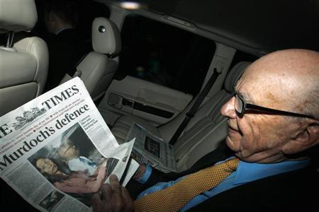 News Corp Chief Executive and Chairman Rupert Murdoch holds a copy of The Times newspaper as he leaves his home in London July 20, 2011. REUTERS/Andrew Winning