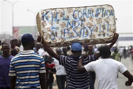 Protesters carry a mattress with the words ''Kill corruption not subsidy'', on the second day of a protest against a removal of fuel subsidies in Lagos January 10, 2012.  REUTERS/Akintunde Akinleye