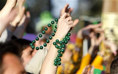 In this file picture, a reveler catches a pair of beads on St. Charles Avenue the weekend before Mardi Gras Day in New Orleans, Louisiana March 6, 2011.REUTERS/Sean Gardner
