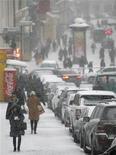 Люди идут по заснеженной Москве 26 декабря 2011 года. Морозная снежная погода не собирается уходить из Москвы в грядущие выходные, ожидают синоптики. REUTERS/Anton Golubev