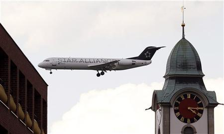 A Fokker 100 of Star Alliance airline is seen behind a church tower during its approach for a landing at Zurich Airport in the town of Kloten April 12, 2011.  REUTERS/Arnd Wiegmann