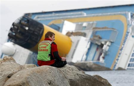A rescue worker sits in front of Costa Concordia cruise ship which ran aground off the west coast of Italy at Giglio island January 19, 2012.  REUTERS/Giampiero Sposito