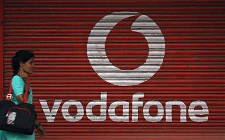 A woman walks past a large logo of Vodafone displayed on a shop in Mumbai May 20, 2010. REUTERS/Arko Datta/Files