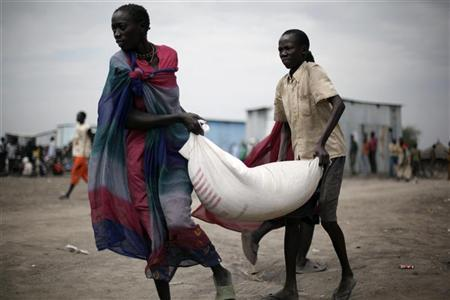 South Sudanese who fled the recent ethnic violence carry food aid from a World Food Programme (WFP) distribution centre in Pibor, Jonglei State, January 12, 2012.  REUTERS/Hereward Holland