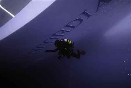 A Carabinieri scuba diver inspects the Costa Concordia cruise ship which ran aground off the west coast of Italy at Giglio island January 19, 2012.   REUTERS/Centro subacquei dei Carabinieri/Handout