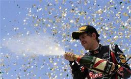 O piloto alemão Sebastian Vettel joga champanhe em pódio de Interlagos, em novembro de 2011. O dono da Red Bull afirmou que Vettel treinou como nunca antes. 27/11/2011 REUTERS/Nacho Doce