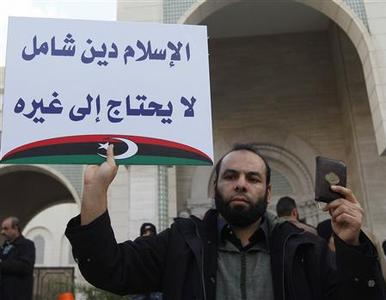 A Libyan Muslim campaigning for sharia law demonstrates in Tripoli's Algeria Square January 20, 2012. The sign reads: ''Islam is a perfect religion, there is no need for any other law''. REUTERS/Ismail Zitouny