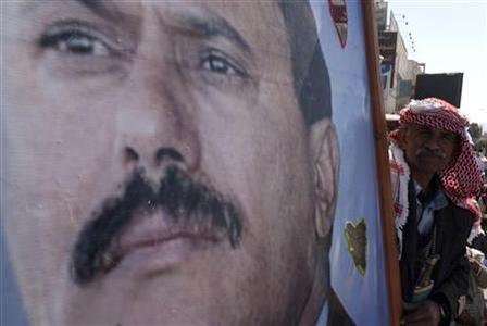 A supporter of Yemen's outgoing President Ali Abdullah Saleh holds his poster as they attend a rally to show support for Saleh in Sanaa January 20, 2012.REUTERS/Mohamed al-Sayaghi