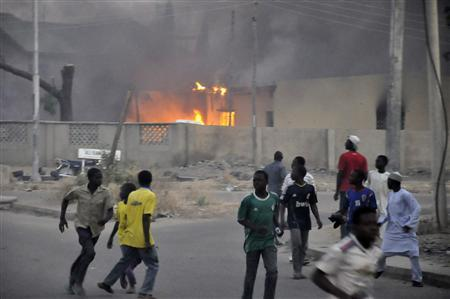 Smoke rises from the police headquarters as people run for safety in Nigeria's northern city of Kano January 20, 2012.  REUTERS/Stringer