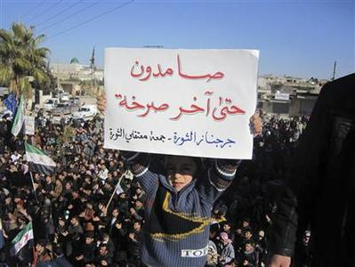 A boy holds up a placard during a protest against Syria's President Bashar al-Assad in Jerjenaz, near Idlib, January 20, 2012. The placard reads, ''Steadfast to the last shout''.   REUTERS/Handout