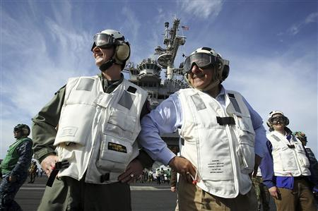 U.S. Defense Secretary Leon Panetta (R), escorted by Commander of Strike Group Twelve Rear Admiral Walter E. Carter Jr. (L), watches day flight operations from the flight deck of the aircraft carrier USS Enterprise off the southeastern coast of the U.S., January 21, 2012. The U.S. will not cut America's fleet of 11 aircraft carriers to help trim the budget deficit, Panetta said on Saturday, citing tensions with Iran as an example of why the massive ships are so critical to national security. REUTERS/Alex Wong/Getty Images/Pool