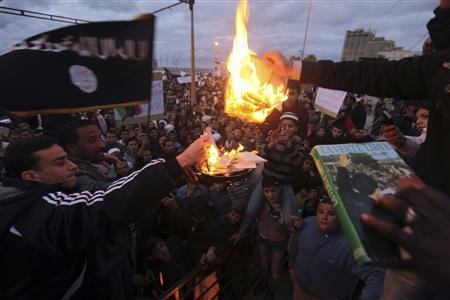 People burn copies of the ''Green Book,'' Muammar Gaddafi's eccentric handbook on politics, economics and everyday life, and pictures of Muammar Gaddafi during a demonstration demanding the Libyan National Transitional Council apply Islamic sharia rule in the country and declare Islam the state religion, in Benghazi January 20, 2012. REUTERS/Esam Al-Fetori