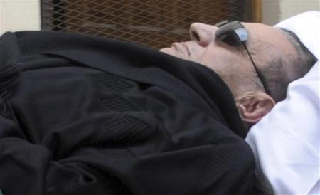 Former Egyptian President Hosni Mubarak is seen on a stretcher outside the courthouse where he is standing trial at the police academy in Cairo January 5, 2012.  REUTERS/Stringer