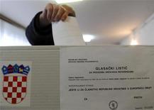 Мужчина бросает бюллетень в урну на участке для голосования в Загребе 22 января 2012 года. Хорватия в воскресенье проголосовала за вступление в Евросоюз в следующем году, проигнорировав опасения по поводу экономических проблем блока и страхи, что он может потерять свою с трудом завоеванную репутацию. REUTERS/ Davor Kovacevic